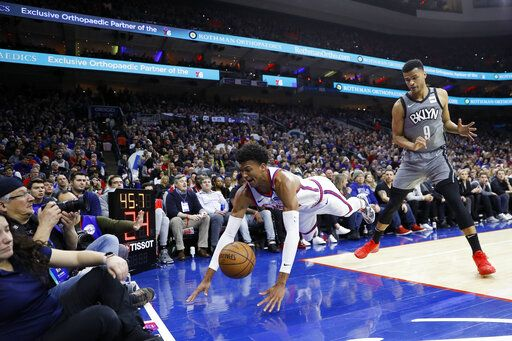Philadelphia 76ers' Matisse Thybulle, center, dives for a loose ball past Brooklyn Nets' Timothe Luwawu-Cabarrot during the first half of an NBA basketball game, Thursday, Feb. 20, 2020, in Philadelphia.