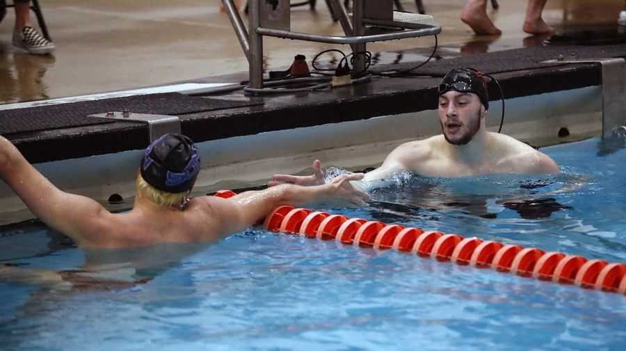Calvin Windle of St. Charles East (right) and Ricky Williams of St. Charles North congratulate each other after competing in the Boys 200 yard Freestyle race Saturday February 22, 2020 during the IHSA Boys Swim and Dive Sectional Championship meet at St. Charles East High School.