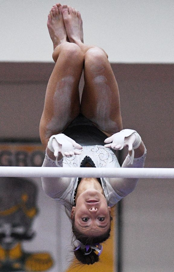 Carmel's Clare Keane on uneven parallel bars at the state girls gymnastics championships at Palatine High School on Saturday.