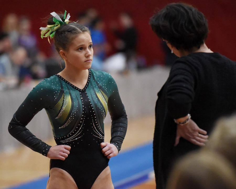 Stevenson's Emily Weinstein gets advice before her performance on vault at the state girls gymnastics championships at Palatine High School on Saturday.