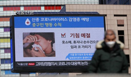 "A huge screen about precautions against the COVID-19 is seen in downtown Seoul, South Korea, Sunday, Feb. 23, 2020. South Korea and China both reported a rise in new virus cases on Sunday, as the South Korean prime minister warned that the fast-spreading outbreak linked to a local church and a hospital in the country's southeast had entered a ""more grave stage."" The screen reads ""Cough etiquette."""