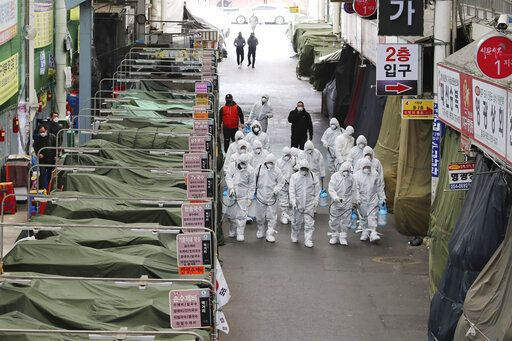 "Workers wearing protective gear spray disinfectant as a precaution against the COVID-19 coronavirus in a local market in Daegu, South Korea, Sunday, Feb. 23, 2020. South Korea's president has put the country on its highest alert for infectious diseases and says officials should take ""unprecedented, powerful"" steps to fight a viral outbreak. (Im Hwa-young/Yonhap via AP)"