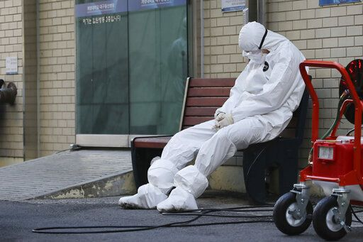 "A member of the medical team takes a rest outside a hospital in Daegu, South Korea, Sunday, Feb. 23, 2020. South Korea's president has put his country on its highest alert for infectious diseases, saying Sunday that officials should take ""unprecedented, powerful"" steps to fight a viral outbreak. (Im Hwa-young/Yonhap via AP)"