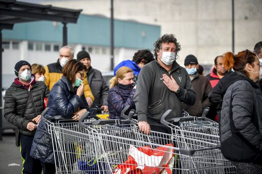 People wearing sanitary masks queue outside a supermarket in Casalpusterlengo, Northern Italy, Sunday, Feb. 23, 2020. A dozen Italian towns saw daily life disrupted after the deaths of two people infected with the virus from China and a pair of case clusters without direct links to the outbreak abroad. A rapid spike in infections prompted authorities in the northern Lombardy and Veneto regions to close schools, businesses and restaurants and to cancel sporting events and Masses. (Claudio Furlan/Lapresse via AP)