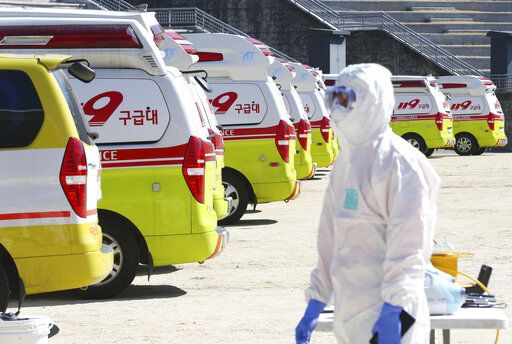 "Ambulances gather as a member of paramedic wearing protective gears walk in Daegu, South Korea, Sunday, Feb. 23, 2020. South Korea's president has put the country on its highest alert for infectious diseases and says officials should take ""unprecedented, powerful"" steps to fight a viral outbreak. (Kim Hyun-tai/Yonhap via AP)"