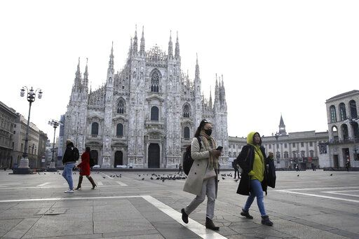 A woman wearing a sanitary mask walks past the Duomo gothic cathedral in Milan, Italy, Sunday, Feb. 23, 2020. A dozen Italian towns saw daily life disrupted after the deaths of two people infected with the virus from China and a pair of case clusters without direct links to the outbreak abroad. A rapid spike in infections prompted authorities in the northern Lombardy and Veneto regions to close schools, businesses and restaurants and to cancel sporting events and Masses.
