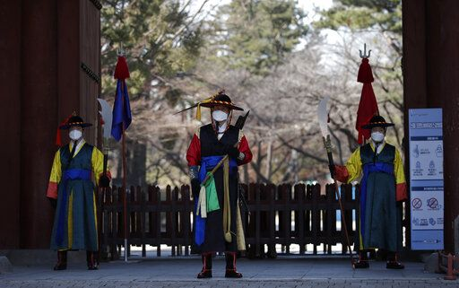 "Officials wearing traditional guard uniforms and masks stand in front of the Deoksu palace in downtown Seoul, South Korea, Sunday, Feb. 23, 2020. South Korea and China both reported a rise in new virus cases on Sunday, as the South Korean prime minister warned that the fast-spreading outbreak linked to a local church and a hospital in the country's southeast had entered a ""more grave stage."""