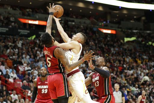 Cleveland Cavaliers guard Dante Exum, center, goes up to shoot against Miami Heat forwards Derrick Jones Jr. (5) and Bam Adebayo (13) during the first half of an NBA basketball game, Saturday, Feb. 22, 2020, in Miami.