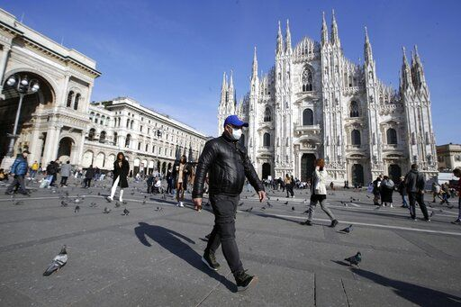 A man wearing a sanitary mask walks past the Duomo gothic cathedral in Milan, Italy, Monday, Feb. 24, 2020. Italy has been scrambling to check the spread of Europe's first major outbreak of the new viral disease amid rapidly rising numbers of infections and calling off the popular Venice Carnival, scrapping major league soccer matches in the stricken area and shuttering theaters, including Milan's legendary La Scala.