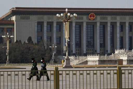 In this Sunday, Feb. 23, 2020, photo, paramilitary policemen wearing protective face masks walk by the empty Tiananmen Square against the back drop of the Great Hall of the People in Beijing. China announced Monday it has postponed its most important political meeting of the year because of the outbreak of the new virus.