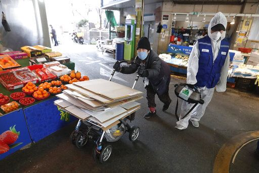 A workers wearing protective gears sprays disinfectant as a precaution against the coronavirus at a market in Seoul, South Korea, Monday, Feb. 24, 2020. South Korean President Moon Jae-in said his government had increased its anti-virus alert level by one notch to 'œRed,'� the highest level. It allows for the temporary closure of schools and reduced operation of public transportation and flights to and from South Korea.