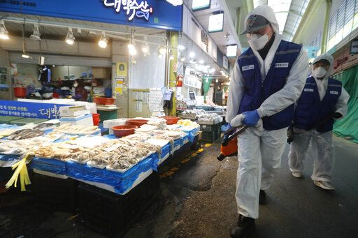 Workers wearing protective gears spray disinfectant as a precaution against the coronavirus at a market in Seoul, South Korea, Monday, Feb. 24, 2020. South Korean President Moon Jae-in said his government had increased its anti-virus alert level by one notch to 'œRed,'� the highest level. It allows for the temporary closure of schools and reduced operation of public transportation and flights to and from South Korea.