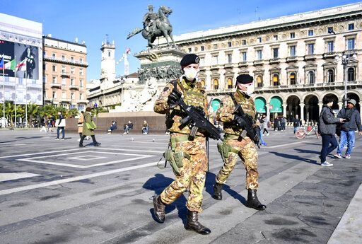 Italian soldiers wearing sanitary masks patrol Duomo square, in downtown Milan, Italy, Monday, Feb. 24, 2020. At least 190 people in Italy's north have tested positive for the COVID-19 virus and four people have died, including an 84-year-old man who died overnight in Bergamo, the Lombardy regional government reported. (Claudio Furlan/Lapresse via AP)