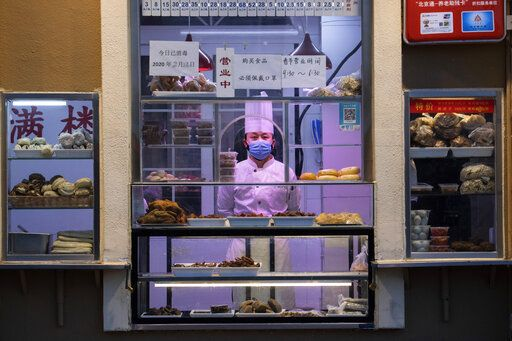 In this photo taken Saturday, Feb. 22, 2020, a chef looks out from behind a display of food products at a restaurant in Beijing, China. Regulators on Monday promised tax cuts and other aid to help companies recover from China's virus outbreak and expressed confidence the ruling Communist Party's growth targets can be achieved despite anti-disease controls that shut down much of the economy.