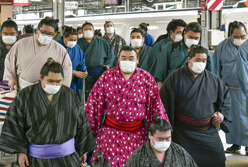 In this Sunday, Feb. 23, 2020, photo, sumo wrestlers wearing masks arrive at Shin Osaka railway station in Osaka, western Japan. A viral outbreak that began in China has infected more than 79,000 people globally. The World Health Organization has named the illness COVID-19, referring to its origin late last year and the coronavirus that causes it.  (Kyodo News via AP)