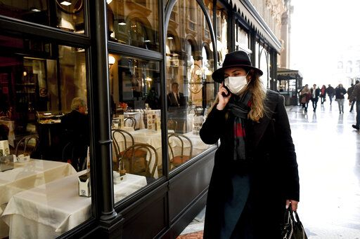 A woman wearing a sanitary mask talks on the phone as she walks in the Vittorio Emanuele Gallery shopping arcade, in downtown Milan, Italy, Monday, Feb. 24, 2020. At least 190 people in Italy's north have tested positive for the COVID-19 virus and four people have died, including an 84-year-old man who died overnight in Bergamo, the Lombardy regional government reported. (Claudio Furlan/Lapresse via AP)