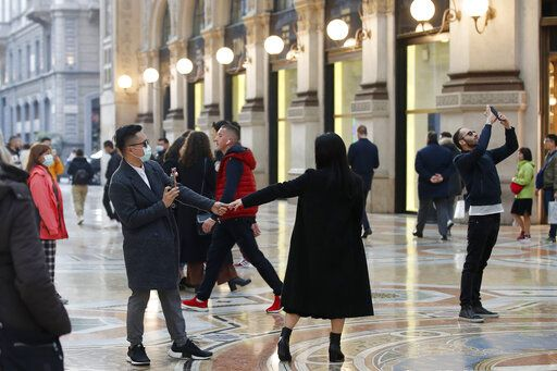 Tourists wearing sanitary masks move a few steps of dance, in downtown Milan, Italy, Sunday, Feb. 23, 2020. In Lombardy, the hardest-hit region with 90 cases Coronavirus infections, schools and universities were ordered to stay closed in the coming days, and sporting events were canceled.