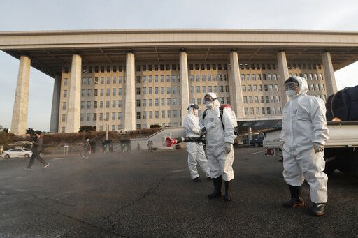 "Workers wearing protective suits spray disinfectant as a precaution against the coronavirus at the National Assembly in Seoul, South Korea, Monday, Feb. 24, 2020. South Korea reported another large jump in new virus cases Monday a day after the the president called for ""unprecedented, powerful"" steps to combat the outbreak that is increasingly confounding attempts to stop the spread."