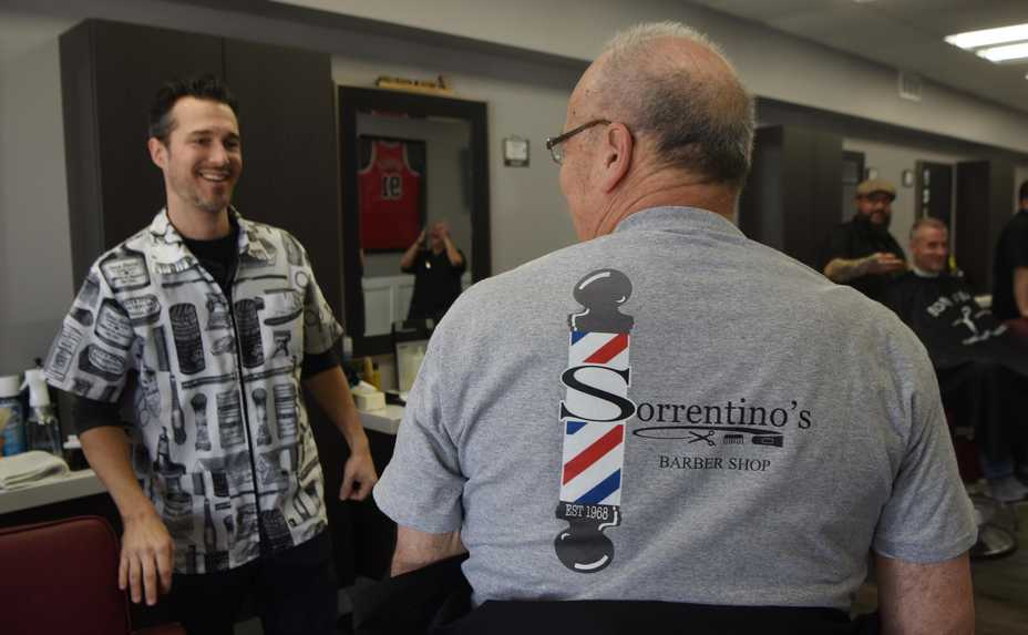 Anthony Imbrogno, from left, owner of Sorrentino's Barber Shop, moved the shop to its new Dunton Avenue location this month. Sporting the business T-shirt with the family name is longtime barber Cesare Sorrentino, who still works there one day a week.