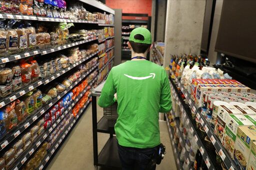 In this Feb. 21, 2020 photo, a worker pushes a cart inside an Amazon Go Grocery store set to open soon in Seattle's Capitol Hill neighborhood. Following the opening of several smaller convenience-type stores using an app and cashier-less technology to tally shoppers' selections, the store will be the first Amazon Go full-sized cashier-less grocery store.