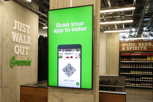In this Feb. 21, 2020 photo, a sign tells shoppers how to check in when they enter an Amazon Go Grocery store set to open soon in Seattle's Capitol Hill neighborhood. Following the opening of several smaller convenience-type stores using an app and cashier-less technology to tally shoppers' selections, the store will be the first Amazon Go full-sized cashier-less grocery store.