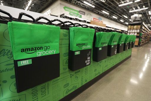 In this Feb. 21, 2020 photo, reusable shopping bags are displayed inside an Amazon Go Grocery store set to open soon in Seattle's Capitol Hill neighborhood. Following the opening of several smaller convenience-type stores using an app and cashier-less technology to tally shoppers' selections, the store will be the first Amazon Go full-sized cashier-less grocery store.