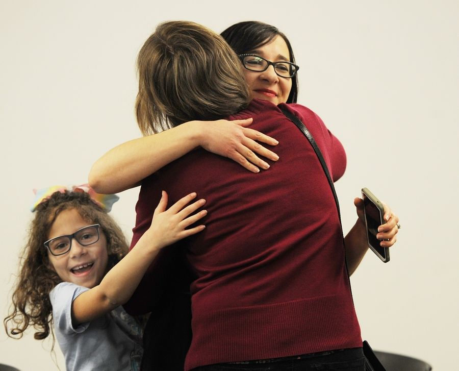 Maria Papanastassiou, the Kids' World assistant manager at the Arlington Heights Memorial Library, is greeted by sister Rhoda Livermore of Mount Prospect and 7-year-old daughter Eliana Jones during a ceremony Tuesday at the library. Papanastassiou is one of 10 winners nationwide of the I Love My Librarian award from the American Library Association.