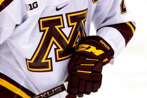 FILE - In this Oct. 25, 2019 file photo, a Minnesota hockey player skates during an NCAA hockey game in Minneapolis. The University of Minnesota says it is investigating allegations that a former men's hockey assistant coach sexually abused players more than 30 years ago.