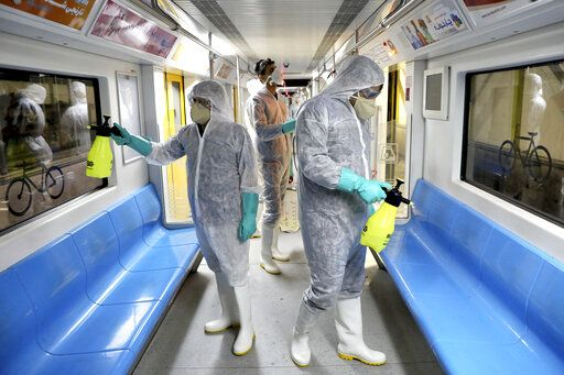 Workers disinfect subway trains against coronavirus in Tehran, Iran, in the early morning of Wednesday, Feb. 26, 2020. Iran's government said Tuesday that more than a dozen people had died nationwide from the new coronavirus, rejecting claims of a much higher death toll of 50 by a lawmaker from the city of Qom that has been at the epicenter of the virus in the country.