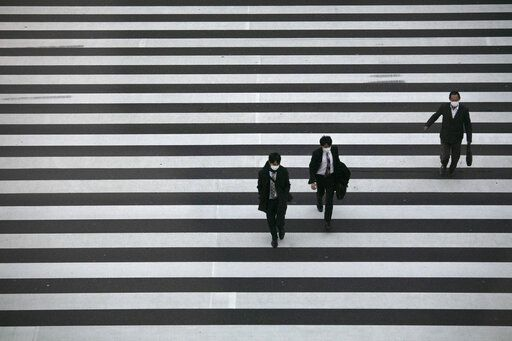 Commuters wearing masks walk across a pedestrian crosswalk Wednesday, Feb. 26, 2020, in Tokyo. At a government task force meeting Wednesday on the virus outbreak, Prime Minister Shinzo Abe said he was asking organizers to cancel or postpone major sports or cultural events over the next two weeks.
