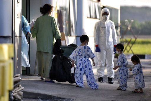 In this photo taken and released by Malaysia's Ministry of Health, a health worker looks at a woman and children arrive at Kuala Lumpur International Airport in Sepang, Malaysia, Wednesday, Feb. 26, 2020, after being evacuated from China's Wuhan, the epicenter of the coronavirus outbreak. U.S. health officials warned Tuesday that the burgeoning coronavirus is certain to spread more widely in the country at some point, even as their counterparts in Europe and Asia scrambled to contain new outbreaks of the illness. (Muzzafar Kasim/Malaysia's Ministry of Health via AP)