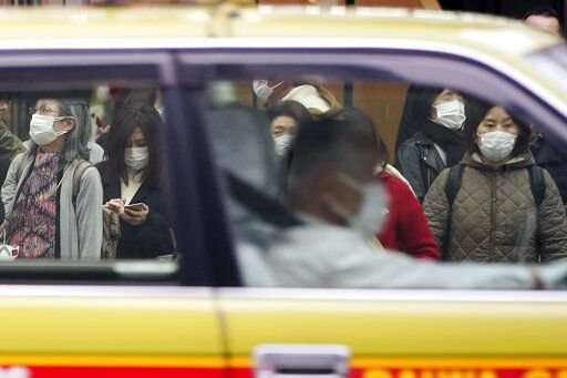 A taxi drives past pedestrians wearing masks as they wait at traffic light in Ginza shopping district Wednesday, Feb. 26, 2020, in Tokyo. At a government task force meeting Wednesday on the virus outbreak, Prime Minister Abe said he was asking organizers to cancel or postpone major sports or cultural events over the next two weeks.