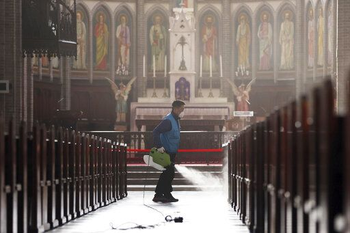 A worker wearing a face mask sprays disinfectant as a precaution against the new coronavirus at Myeongdong Cathedral in Seoul, South Korea, Wednesday, Feb. 26, 2020. The number of new virus infections in South Korea jumped again Wednesday and the U.S. military reported its first case among its soldiers based in the Asian country, with his case and many others connected to a southeastern city with an illness cluster. (Lee Ji-eun/Yonhap via AP)