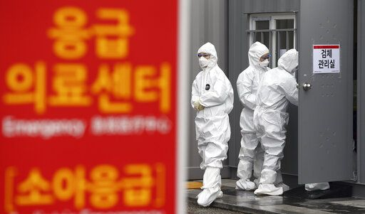 "Officials wearing protective attire work to diagnose people with suspected symptoms of the new coronavirus at a hospital in Daegu, South Korea, Wednesday, Feb. 26, 2020. The number of new virus infections in South Korea jumped again Wednesday and the U.S. military reported its first case among its soldiers based in the Asian country, with his case and many others connected to a southeastern city with an illness cluster. A sign reads ""Emergency Medical Center."" (Kim Hyun-tae/Yonhap via AP)"