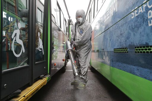A worker wearing a protective suit sprays disinfectant as a precaution against the coronavirus at a bus garage in Seoul, South Korea, Wednesday, Feb. 26, 2020. The number of new virus infections in South Korea jumped again Wednesday and the U.S. military reported its first case among its soldiers based in the Asian country, with his case and many others connected to a southeastern city with an illness cluster.