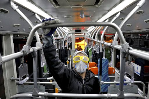 A worker disinfects a public bus against coronavirus in Tehran, Iran, in early morning of Wednesday, Feb. 26, 2020. Iran's government said Tuesday that more than a dozen people had died nationwide from the new coronavirus, rejecting claims of a much higher death toll of 50 by a lawmaker from the city of Qom that has been at the epicenter of the virus in the country.
