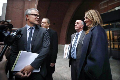 Attorney John Littrell, left, speaks to the media as client Michelle Janavs, right, stands beside attorney Thomas Bienert, second from right, outside federal court, Tuesday, Feb. 25, 2020, in Boston. Janavs was sentenced to five months in prison for trying to cheat and bribe her daughters' way into college as part of a nationwide college cheating scam.