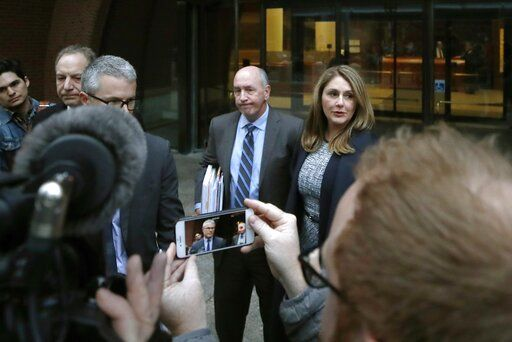 Attorney John Littrell, left and on the screen at center, speaks to the media as client Michelle Janavs, right, stands beside attorney Thomas Bienert, second from right, outside federal court, Tuesday, Feb. 25, 2020, in Boston. Janavs was sentenced to five months in prison for trying to cheat and bribe her daughters' way into college as part of a nationwide college cheating scam.