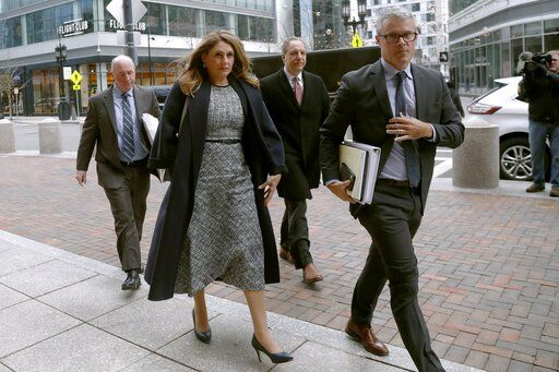Michelle Janavs arrives with her attorneys at federal court, Tuesday, Feb. 25, 2020, in Boston, for sentencing in a nationwide college admissions bribery scandal.
