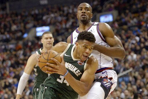 Milwaukee Bucks forward Giannis Antetokounmpo (34) drives past Toronto Raptors center Serge Ibaka (9) during the first half of an NBA basketball game Tuesday, Feb. 25, 2020, in Toronto. (Nathan Denette/The Canadian Press via AP)