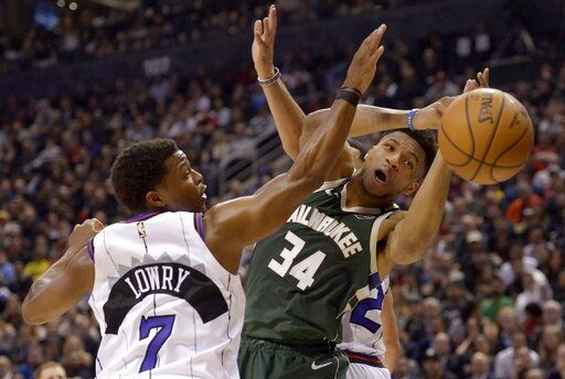 Toronto Raptors guard Kyle Lowry (7) and Milwaukee Bucks forward Giannis Antetokounmpo (34) vie for a loose ball during the first half of an NBA basketball game Tuesday, Feb. 25, 2020, in Toronto. (Nathan Denette/The Canadian Press via AP)