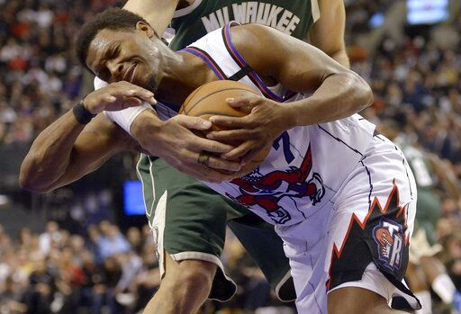 Toronto Raptors guard Kyle Lowry (7) is fouled by Milwaukee Bucks center Brook Lopez during the first half of an NBA basketball game Tuesday, Feb. 25, 2020, in Toronto. (Nathan Denette/The Canadian Press via AP)