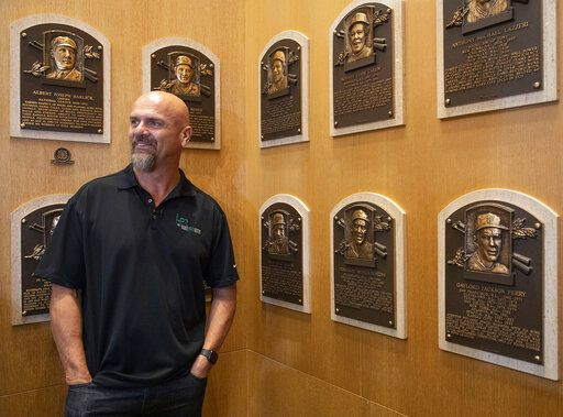 "In this photo provided by the National Baseball Hall of Fame and Museum, Larry Walker poses near the wall of plaques, Tuesday, Feb. 25, 2020 at the National Baseball Hall of Fame in Cooperstown, N.Y. Walker said on Tuesday that his Hall of Fame plaque will show him in Colorado Rockies cap, not a Montreal Expos hat. He added the key to picking the Rockies is that Colorado was ""where the majority of my damage was done."" (Milo Stewart, Jr./National Baseball Hall of Fame and Museum via AP)"