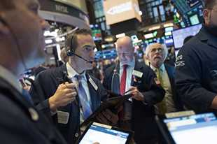 Stock traders work Wednesday at the New York Stock Exchange.