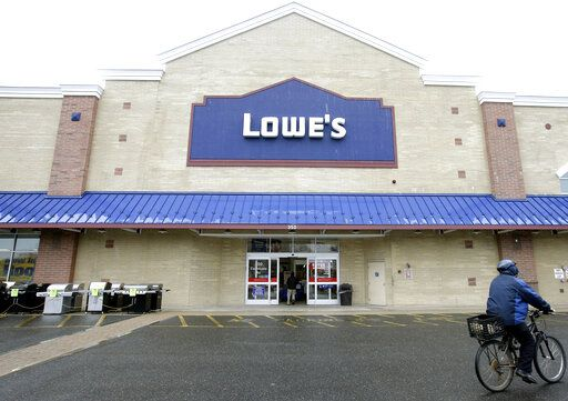 FILE - In this Feb. 23, 2018, file photo a cyclist rides near an entrance to a Lowe's retail home improvement and appliance store, in Framingham, Mass. Lowe's Cos. delivered weaker-than-expected sales for the fiscal fourth quarter and offered an annual forecast that came below Wall Street expectations. The report, issued Wednesday, Feb. 26, 2020, sent shares down in early morning trading.