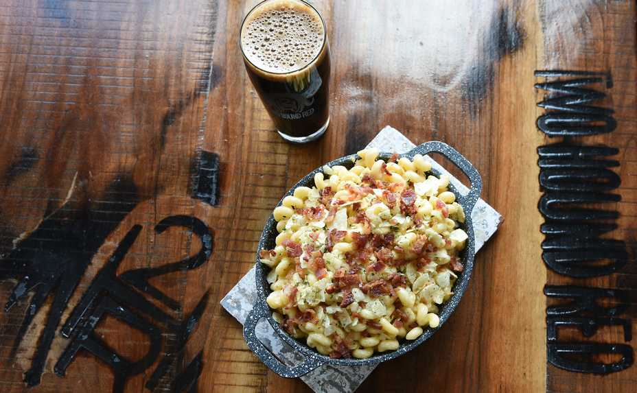 The Mac + Cheese — paired here with a Stoaty-Oaty-Licious American Oatmeal Stout — draws flavor from smoked Gouda, bacon and potato chip crumbles at Two Hound Red in Glen Ellyn.