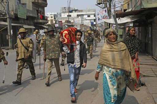 An Indian Muslim family leaves the area as Indian paramilitary soldiers patrol a street vandalized in Tuesday's violence in New Delhi, India, Thursday, Feb. 27, 2020. India accused a U.S. government commission of politicizing communal violence in New Delhi that killed at least 30 people and injured more than 200 as President Donald Trump was visiting the country. The violent clashes between Hindu and Muslim mobs were the capital's worst communal riots in decades and saw shops, Muslim shrines and public vehicles go up in flames.