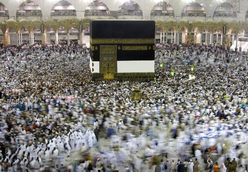 FILE - In this Aug. 7, 2019, file photo, Muslim pilgrims circumambulate around the Kaaba, the cubic building at the Grand Mosque, ahead of the Hajj pilgrimage in the Muslim holy city of Mecca, Saudi Arabia. Saudi Arabia on Thursday, Feb. 27, 2020, halted travel to the holiest sites in Islam over fears of the global outbreak of the new coronavirus just months ahead of the annual hajj pilgrimage, a move coming as the Mideast has over 220 confirmed cases of the illness.
