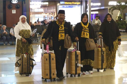 Indonesian who are scheduled to travel to Saudi Arabia for a minor pilgrimage, called 'Umrah', walk with their luggages as they are turned away from their flights at Soekarno-Hatta International Airport in Tangerang, Indonesia, Thursday, Feb. 27, 2020. Saudi Arabia on Thursday banned foreign pilgrims from entering the kingdom to visit Islam's holiest sites over the new coronavirus, potentially disrupting the plans of millions of faithful ahead of the Muslim fasting month of Ramadan and as the annual hajj pilgrimage looms.