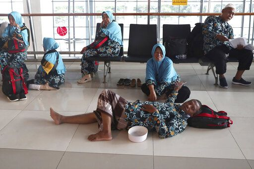 Indonesian who are scheduled to travel to Saudi Arabia for a minor pilgrimage, called 'Umrah', rest at a waiting area as they are turned away from their flights at Soekarno-Hatta International Airport in Tangerang, Indonesia, Thursday, Feb. 27, 2020. Saudi Arabia on Thursday banned foreign pilgrims from entering the kingdom to visit Islam's holiest sites over the new coronavirus, potentially disrupting the plans of millions of faithful ahead of the Muslim fasting month of Ramadan and as the annual hajj pilgrimage looms.